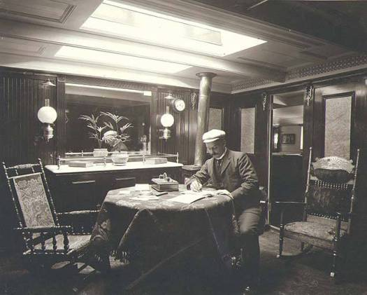 Crew_member_seated_at_a_desk_in_one_the_interior_cabins_of_the_fourmasted_British_bark_GRENADA_Washington_ca_1904
