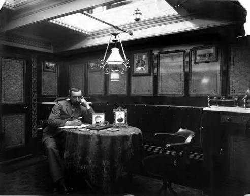 Man_writing_at_a_table_interior_of_an_unidentified_ship_Washington_ca_1900