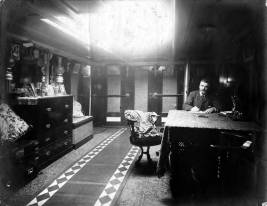 Man_writing_at_desk_interior_of_unidentified_ship_Washington_ca_1900