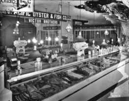 The Pacific Oyster & Fish Co., stall 145-6 in the Crystal Palace Market, ca. 1927. The company was owned and operated by the Victor brothers- George, Steve and William.